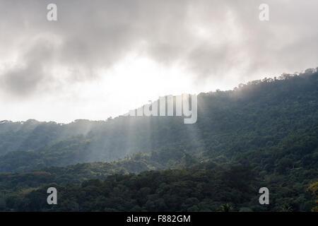 Crepuscular rays, sunshine passing through the mountains, Vila do Abraao, Ilha Grande, Angra dos Reis, State of - Stock Photo