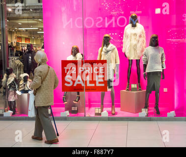 Elderly lady walking past sale sign in River Island store in Eldon Square shopping centre, Newcastle upon Tyne. - Stock Photo