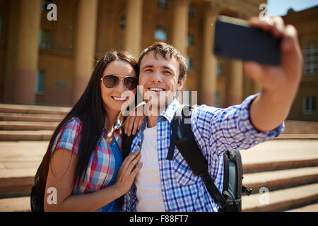 Couple of tourists making selfie against the beautiful building - Stock Photo