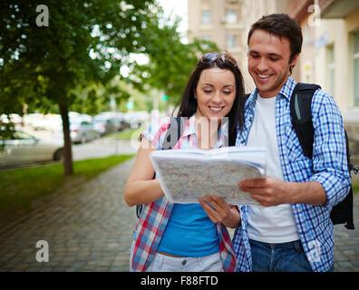 Smiling couple with map in the city - Stock Photo