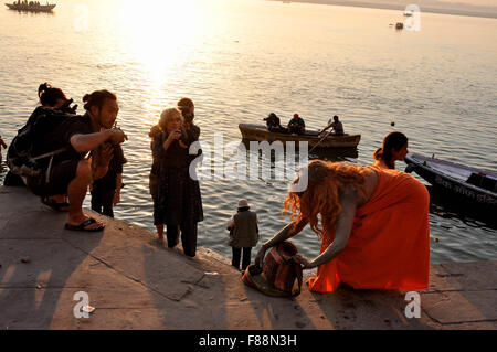 On Kumbh, a foreign devotee after taking bath in Holy River Ganges and some tourists at Ghat  in Varanasi, Uttar - Stock Photo