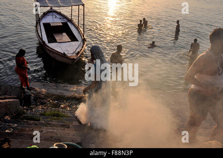 Devotees taking bath and a women burning some waste material at the bank of Holy River Ganges in Varanasi, Uttar - Stock Photo