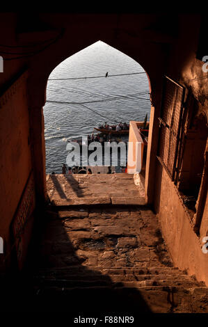 View from an old building gate some pilgrims using boats to cross Holy River ganges to reach their destination in - Stock Photo