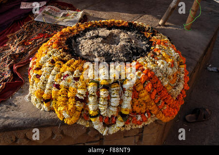 Devoteies and Sadhus use beautifully designed fire- place with marigold garlands on the bank of Holy river Ganges - Stock Photo