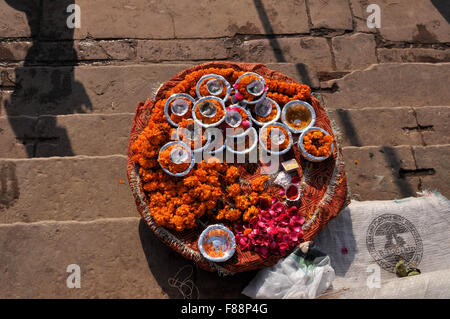 On religious ceremonies Hindu devotees use marigold and rose flowers , cotton, ghee, sweets, red powder, and Ganga - Stock Photo