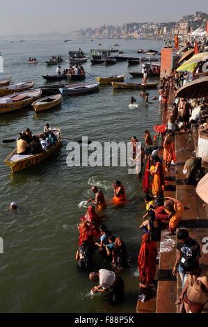 Hindu devotees praying in knee deep ganga water at Ghat in Varanasi. Varanasi is the second oldest city in the world, - Stock Photo