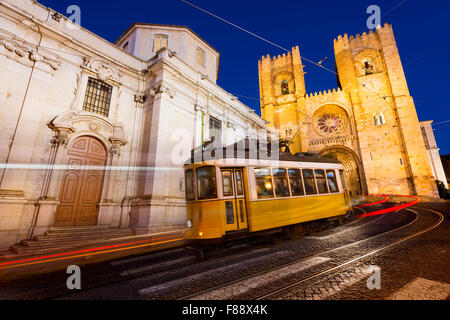 Tram in front of the Lisbon Cathedral at night - Stock Photo