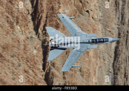Close Up Shot Of A Royal Air Force Tornado GR4 Jet Fighter Turning Sharply Through A Desert Valley. - Stock Photo