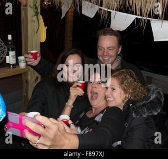Family members taking a cell phone selfie while enjoying a backyard Tiki Bar. Downers Grove Illinois IL USA - Stock Photo