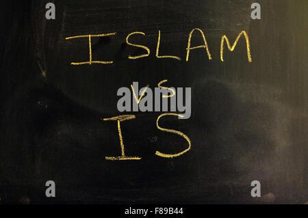 Islam vs IS written on a blackboard in chalk. - Stock Photo