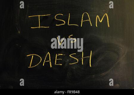 Islam vs Daesh written on a blackboard in chalk. - Stock Photo