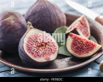 Ripe fig fruits on in the old tray on the wooden table. - Stock Photo