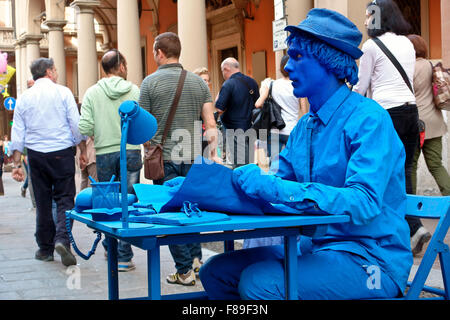 Blue painted man street performer, human statue, sitting still at a desk, on a busy street. Office in the street. - Stock Photo