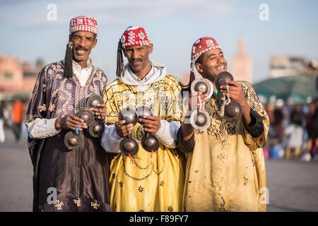 Three Gnawa musicians in traditional dress performing at Jemaa el-Fnaa in Marrakesh - Stock Photo