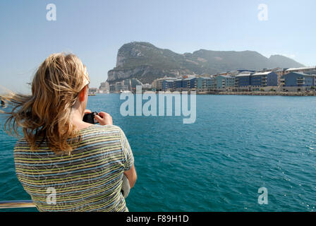 Gibraltar from the sea with the Rock in the background and new development in the middle ground. Tourist in foreground. - Stock Photo