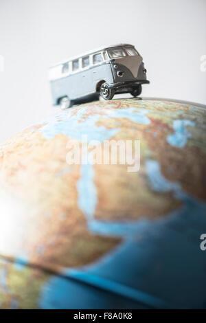 Vintage VW bus on globe. Miniature concept - Stock Photo
