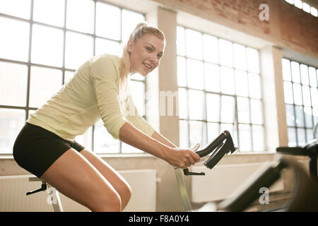 Indoor shot of a sportive woman on bicycle in gym. Young female athlete working out on spinning bike at health club. - Stock Photo
