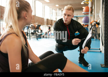 Young woman in a gym sitting on floor and talking to her private trainer about exercise plan - Stock Photo