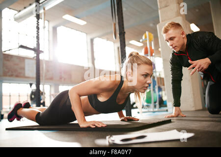 Indoor shot of young female exercising with personal trainer at gym. Fitness woman doing push ups with her personal - Stock Photo