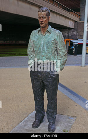 A life size man moulded from concrete and painted standing facing another concrete man at the side of the Grand - Stock Photo