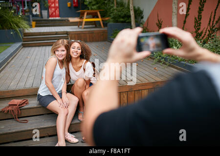 Two young woman sitting together posing for a photo being taking by their friend. Man taking photographs of his - Stock Photo