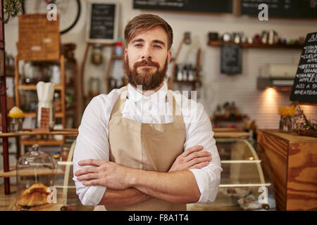 Portrait of young man wearing apron standing with his arms crossed in a coffee shop. Caucasian man with beard standing - Stock Photo