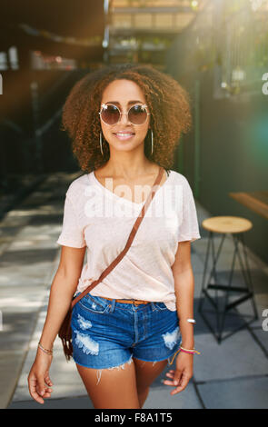 Stylish african woman wearing sunglasses posing outdoors. Beautiful young girl with curly hair in casuals walking - Stock Photo