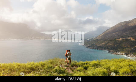 Young couple in love standing on hill, with beautiful view of bay and mountain range in background. Couple on romantic - Stock Photo