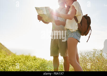 Young couple looking at map while standing outdoors in countryside with bright sunshine from behind. Couple looking - Stock Photo