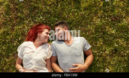 Overhead view of happy young couple in love relaxing on the grass. Affectionate young man and woman lying on grass - Stock Photo