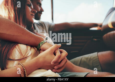 Affectionate young couple sitting in back seat of a car going on road trip. Focus on couple holding hands. - Stock Photo