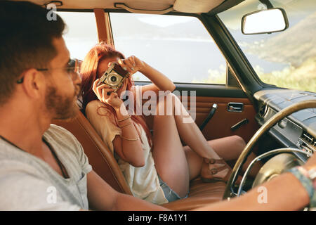 Caucasian couple going on a road trip. Woman taking pictures with camera and man driving car. - Stock Photo