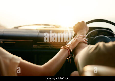 Rear view of a young couple holding hands while sitting in their car together. Man and woman on a road trip. - Stock Photo
