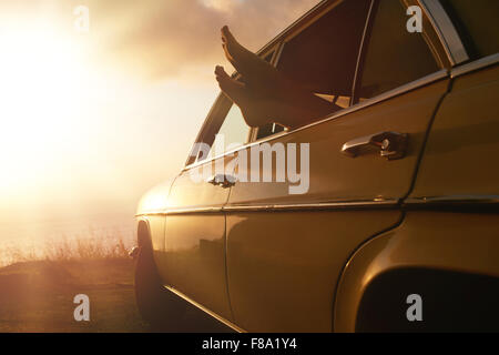 Shot of woman relaxing in a car on road trip. Female feet hanging out of vehicle window at sunset. - Stock Photo