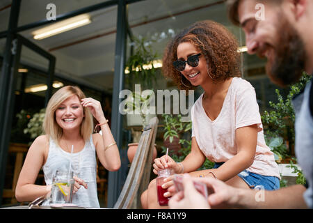 Three friends sitting at sidewalk cafe and playing cards. Relaxed young people at coffee shop enjoying in their free time. Women Stock Photo