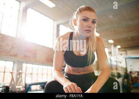 Portrait of attractive young woman sitting relaxed after her workout at gym. Fitness female taking break after exercising - Stock Photo