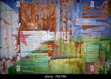 An abstract background image of the flag of Djibouti painted on to rusty corrugated iron sheets overlapping to form - Stock Photo