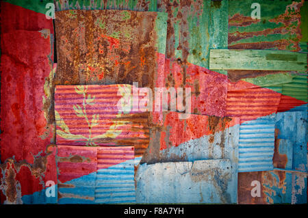 An abstract background image of the flag of Eritrea painted on to rusty corrugated iron sheets overlapping to form - Stock Photo