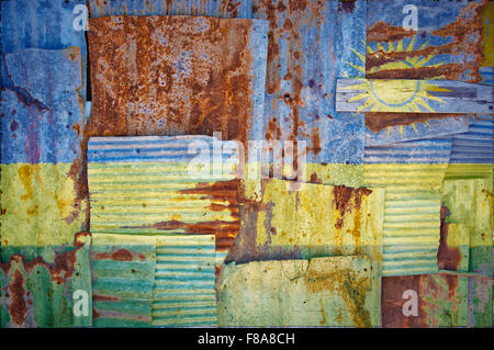 An abstract background image of the flag of Rwanda painted on to rusty corrugated iron sheets overlapping to form - Stock Photo