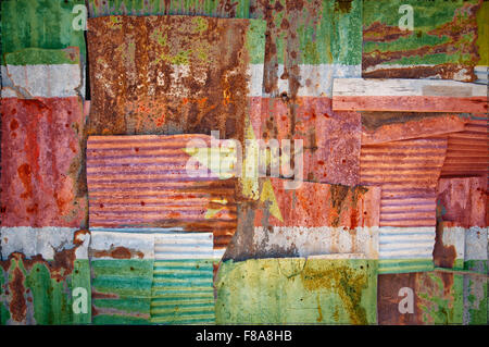 An abstract background image of the flag of Suriname painted on to rusty corrugated iron sheets overlapping to form - Stock Photo