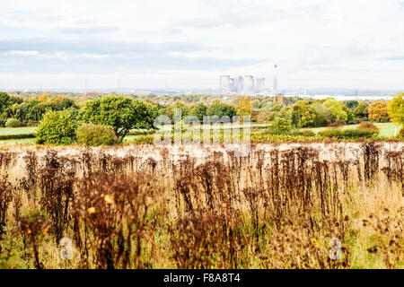 Fiddlers Ferry Power Station in the distance through the haze viewed across fields from Daresbury Firs - Stock Photo