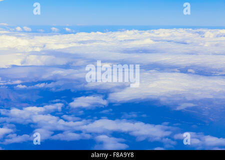 View on blue sky above white clouds from the window of airplane - Stock Photo