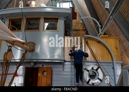 Boy climbing ladder on the RCMP St. Roch schooner, Vancouver Maritime Museum, Vancouver, BC, Canada - Stock Photo