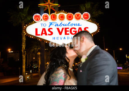 Bride and groom kissing in front of the historic Welcome to Fabulous Las Vegas Nevada sign at night. - Stock Photo