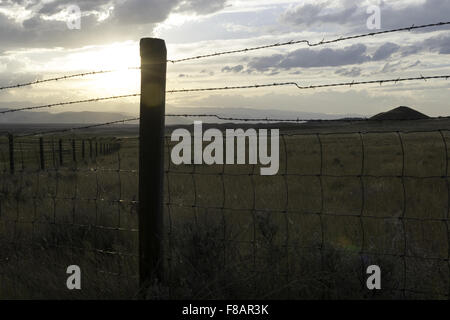 A wooden post and wire cattle fence leads off into the sun setting behind a mountain range in rural Wyoming. - Stock Photo