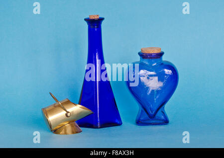 Two decorative blue glass bottles with decorative brass object on blue background - Stock Photo