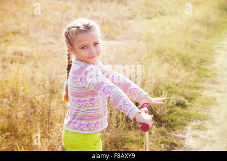 Beautiful girl driving scooter on rural road - Stock Photo
