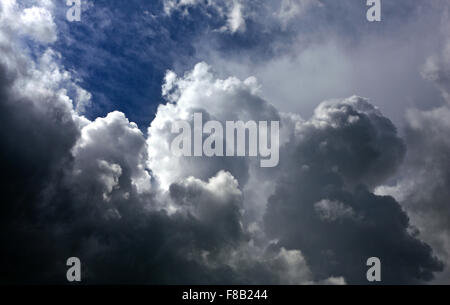Clouds in the sky. Sunshine or rain, showers. Fluffy dark clouds, dramatic down to the left. - Stock Photo