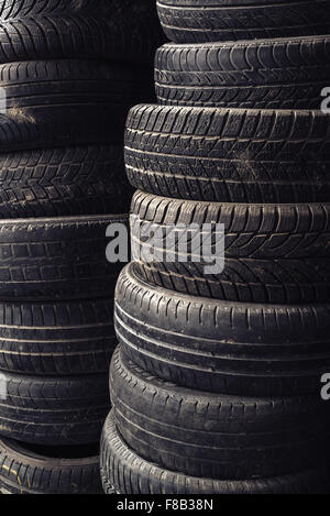 Column stack of old used car tires in secondary car parts shop garage. - Stock Photo
