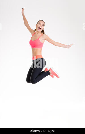 Happy joyful young fitness woman in pink top and black leggings jumping over white background - Stock Photo
